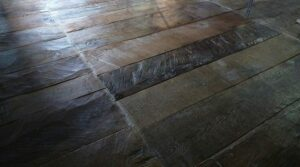 Hand hewn plank floor similar to the first forms of wood flooring.