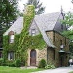 Ivy covered stone tudor. Note the slight flair of the roof at the soffit (a distinct dutch influence)