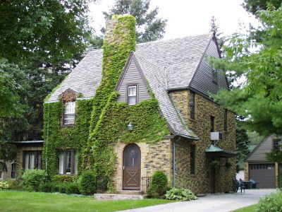 Ivy covered stone tudor. Note the slight flair of the roof at the soffit (