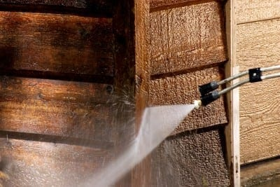 Safely washing old wood siding using a low-pressure washer.